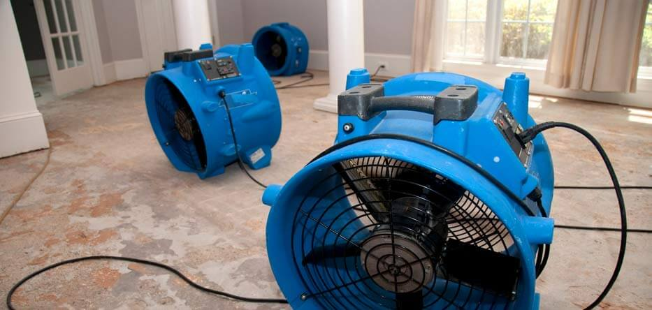 Photograph of two large blue fans used to dry out a house that has been flooded