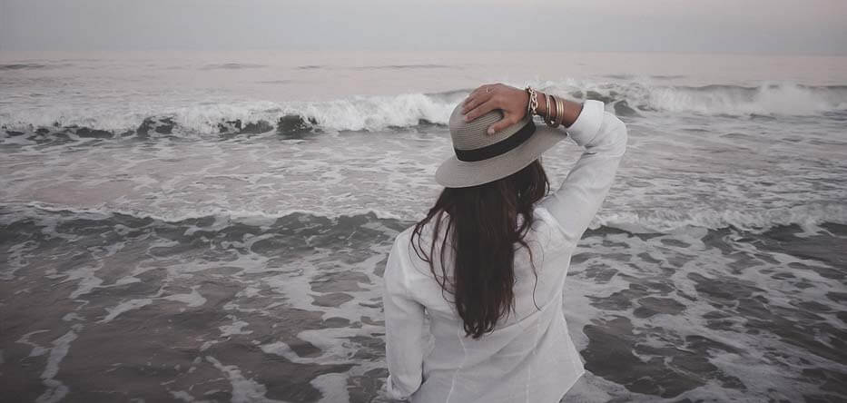 Woman holding hat on head looking out into the ocean