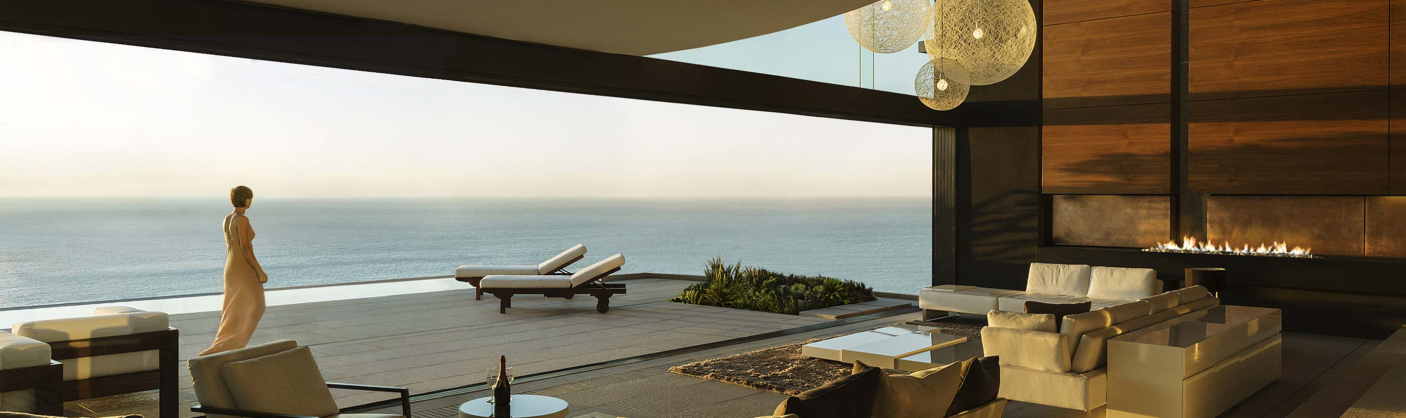 woman walking on the terrace of a luxury home overlooking the ocean