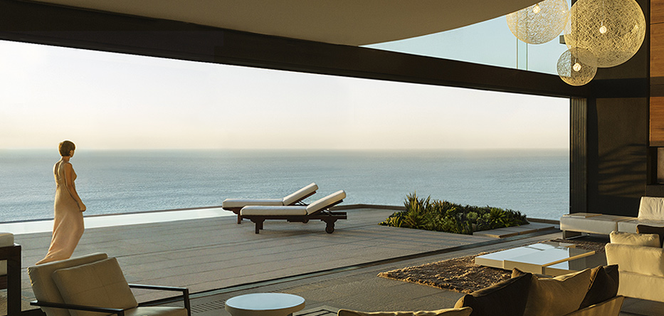 Elegant woman strolls on the terrace of a luxury home with sweeping ocean views