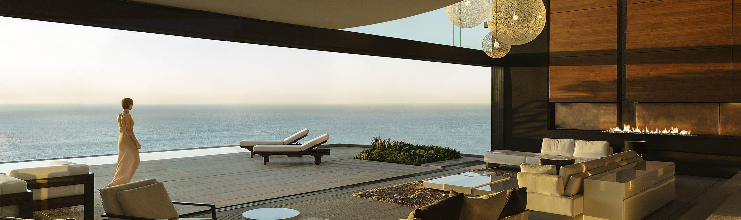Elegant woman strolls on the terrace of a modern home with sweeping ocean views.
